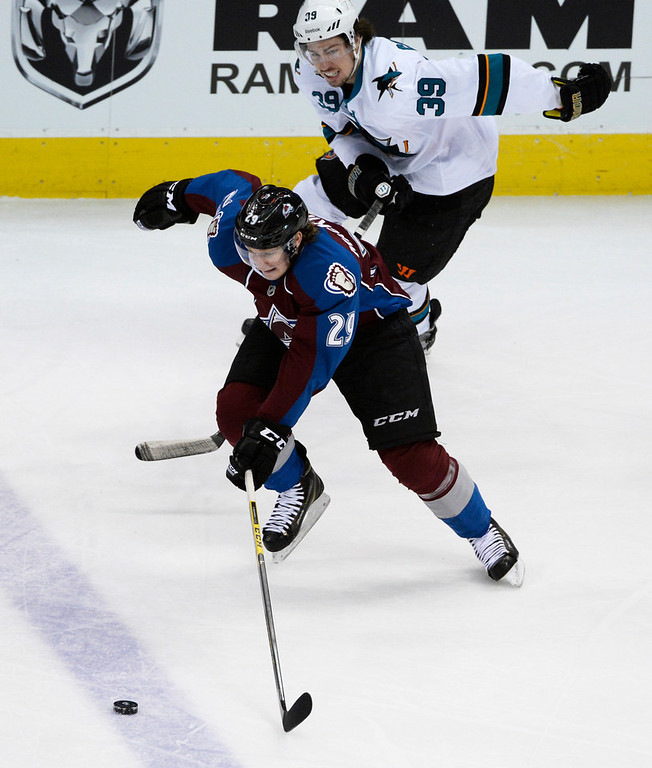 . Colorado Avalanche center, Nathan MacKinnon, left, goes after a loose puck against Logan Couture, San Jose Sharks, the first period of play Saturday afternoon at the Pepsi Center March 29, 2014. (Photo By Andy Cross / The Denver Post)