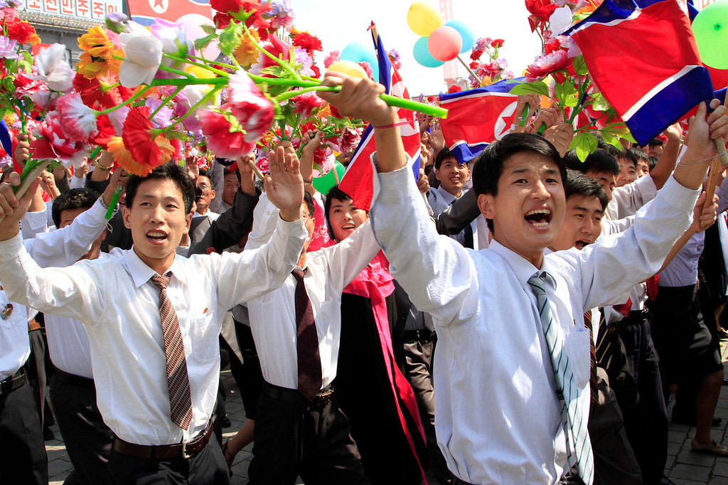 . North Koreans cheer and wave their national flag during a military parade at Kim Il Sung Square to mark the 65th anniversary of the country\'s founding in Pyongyang, North Korea, Monday, Sept. 9, 2013. (AP Photo/Jon Chol Jin)