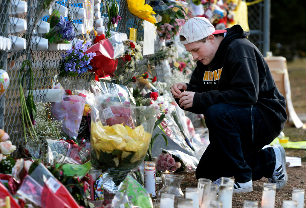 . Senior Mat Lowe lights a candle at the tribute area before visiting Arapahoe High School in Centennial, CO December 19, 2013. Seniors and Juniors returned to the school for two hour periods Thursday, Sophomores and Freshmen will return on Friday. (Photo By Craig F. Walker / The Denver Post)