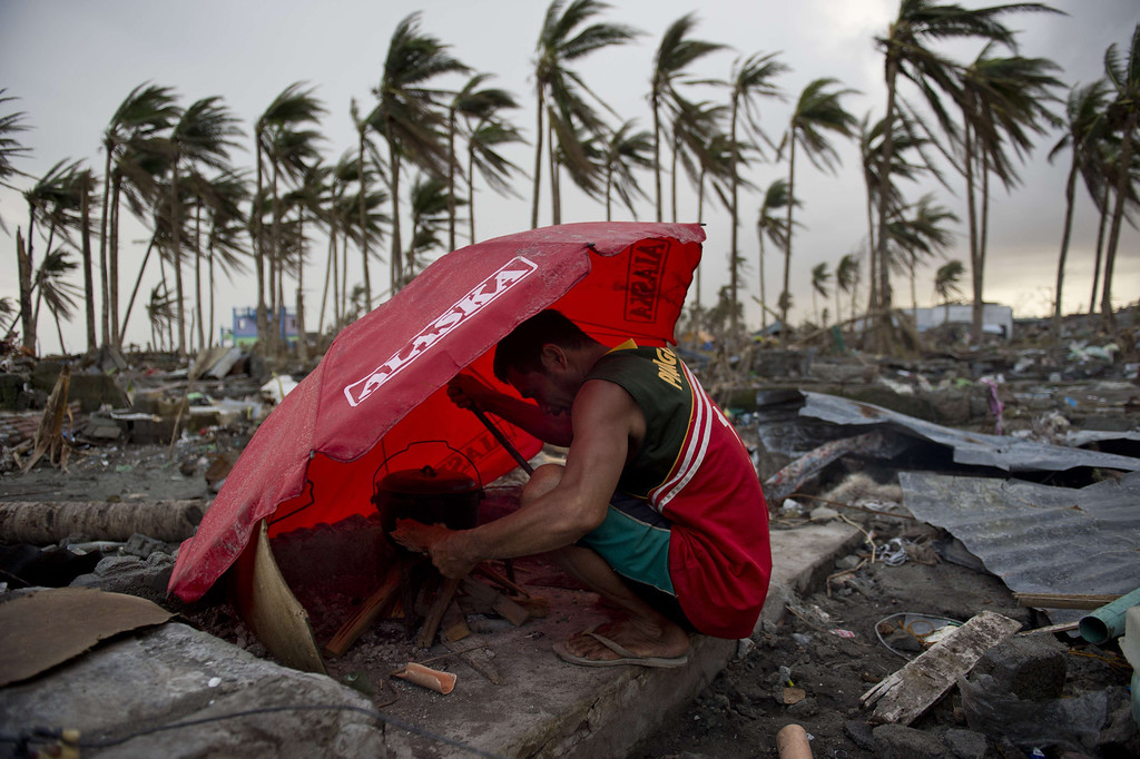 . A man uses an umbrella to shelter from the wind as he tries to light a fire amid the rubble of destroyed homes in Tacloban, Philippines on November 21, 2013.   AFP PHOTO / ODD ANDERSEN/AFP/Getty Images