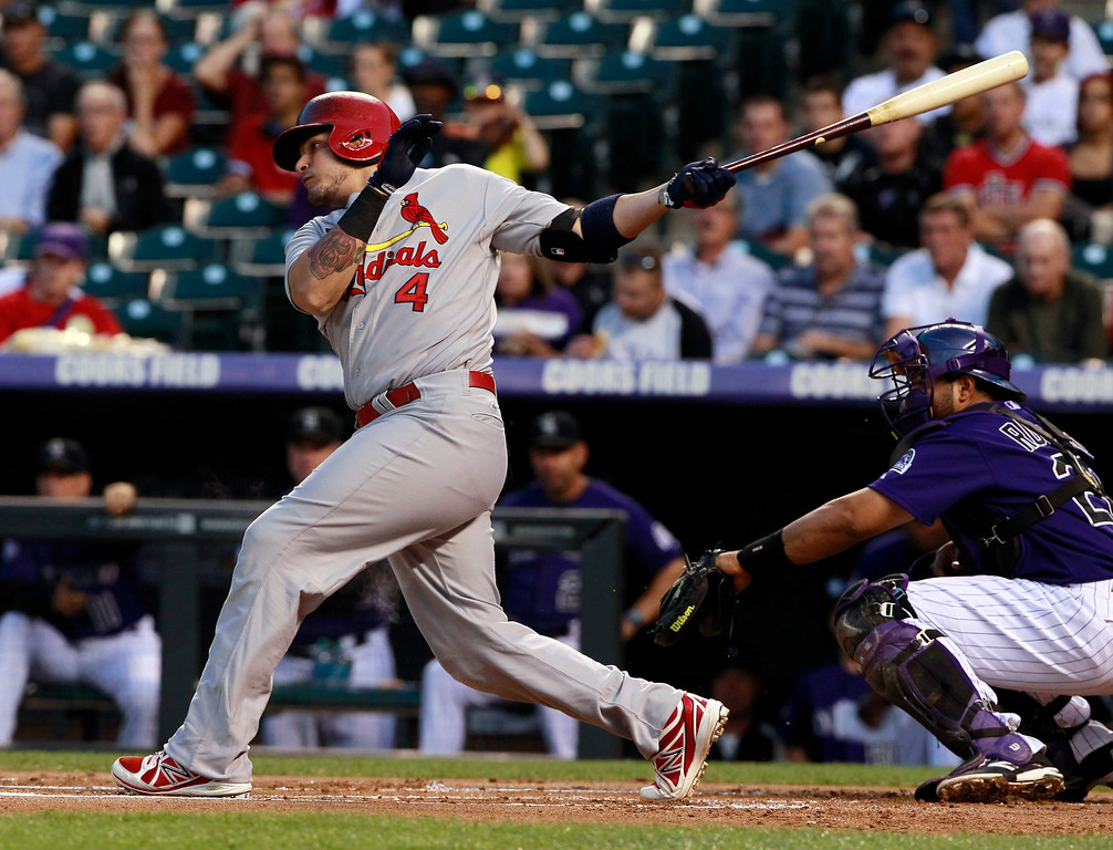 . St. Louis Cardinals\' Yadier Molina, left, follows the flight of his RBI single as Colorado Rockies catcher Wilin Rosario watches in the first inning of a baseball game in Denver on Tuesday, Sept. 17, 2013. (AP Photo/David Zalubowski)