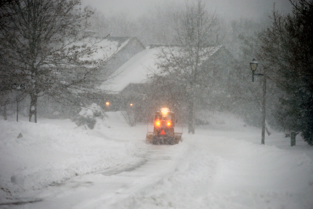 . A small plow clears snow in Newtown Twp., Pa., Thursday, Feb. 13, 2014. A winter storm dumped more than a foot of snow in parts of the Mid-Atlantic region as it marched Northeast and threatened more power outages, traffic headaches and widespread closures for millions of residents.  (AP Photo/Mel Evans)