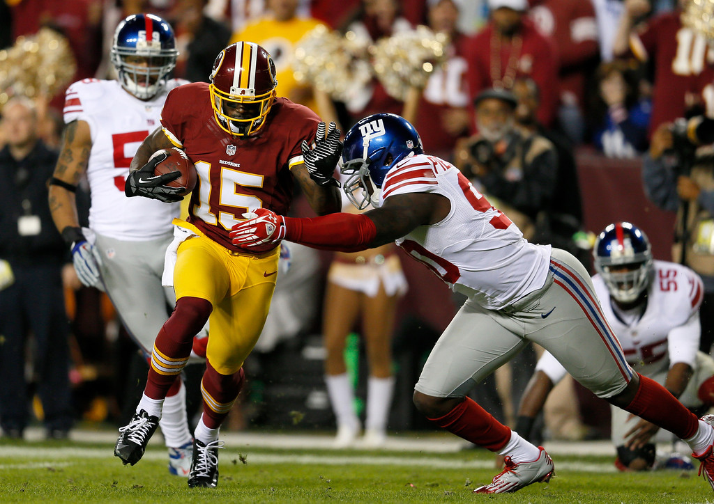 . LANDOVER, MD - DECEMBER 03:  Josh Morgan #15 of the Washington Redskins runs the ball as he is hit by Jason Pierre-Paul #90 of the New York Giants before he scores a touchdown after recovering a fumble by Robert Griffin III #10 in the first quarter at FedExField on December 3, 2012 in Landover, Maryland.  (Photo by Rob Carr/Getty Images)