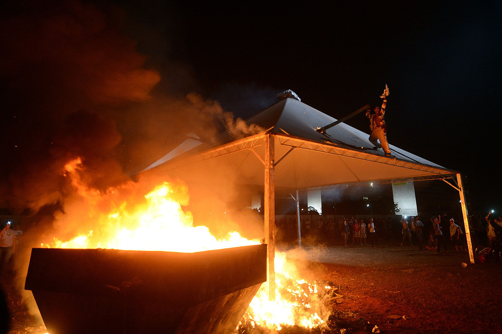 . Demonstrators set a stand on fire while debris burn during a protest of what is now called the \'Tropical Spring\' against corruption and price hikes, at National Congress in Brasilia, on June 20, 2013.  AFP PHOTO / Evaristo  SA/AFP/Getty Images