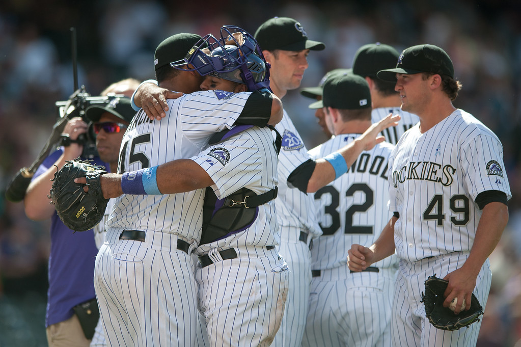 . DENVER, CO - JUNE 16:  Jhoulys Chacin #45 and Wilin Rosario #20 of the Colorado Rockies embrace as Rex Brothers #49 looks on after a win over the Philadelphia Phillies at Coors Field on June 16, 2013 in Denver, Colorado. The Rockies beat the Phillies 5-2. (Photo by Dustin Bradford/Getty Images)