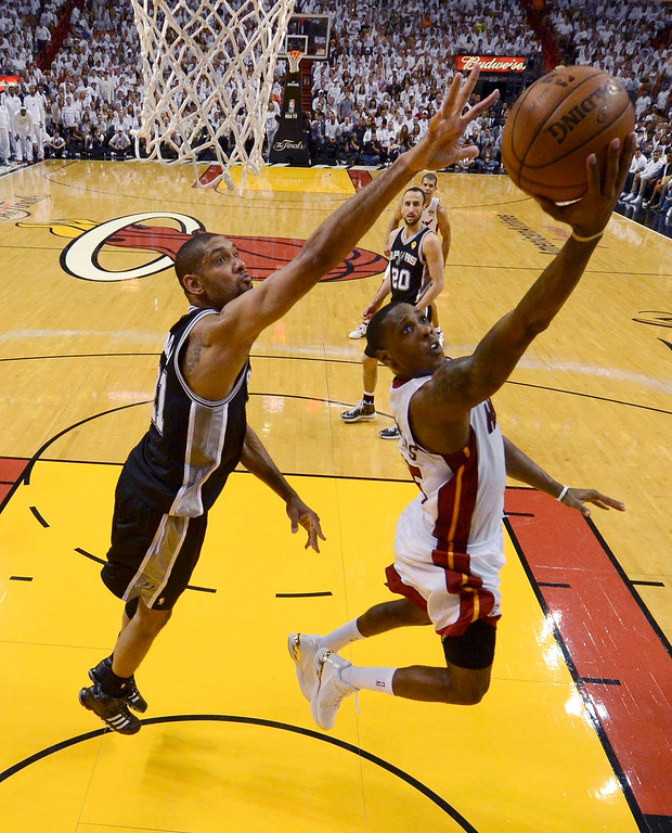 . Miami Heat point guard Mario Chalmers (15) scores on a play past San Antonio Spurs power forward Tim Duncan (21) during Game 7 of their NBA Finals basketball playoff in Miami, Florida June 20, 2013. REUTERS/Steve Mitchell/Pool