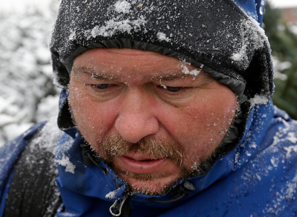 . Jim Cline face is covered in snot as he removes snow from Christmas trees for shoppers following a winter storm Friday, Dec. 6, 2013, in Indianapolis. Several inches of snow fell on central and southern Indiana, making driving treacherous and leading to at least two fatal crashes. (AP Photo/Darron Cummings)