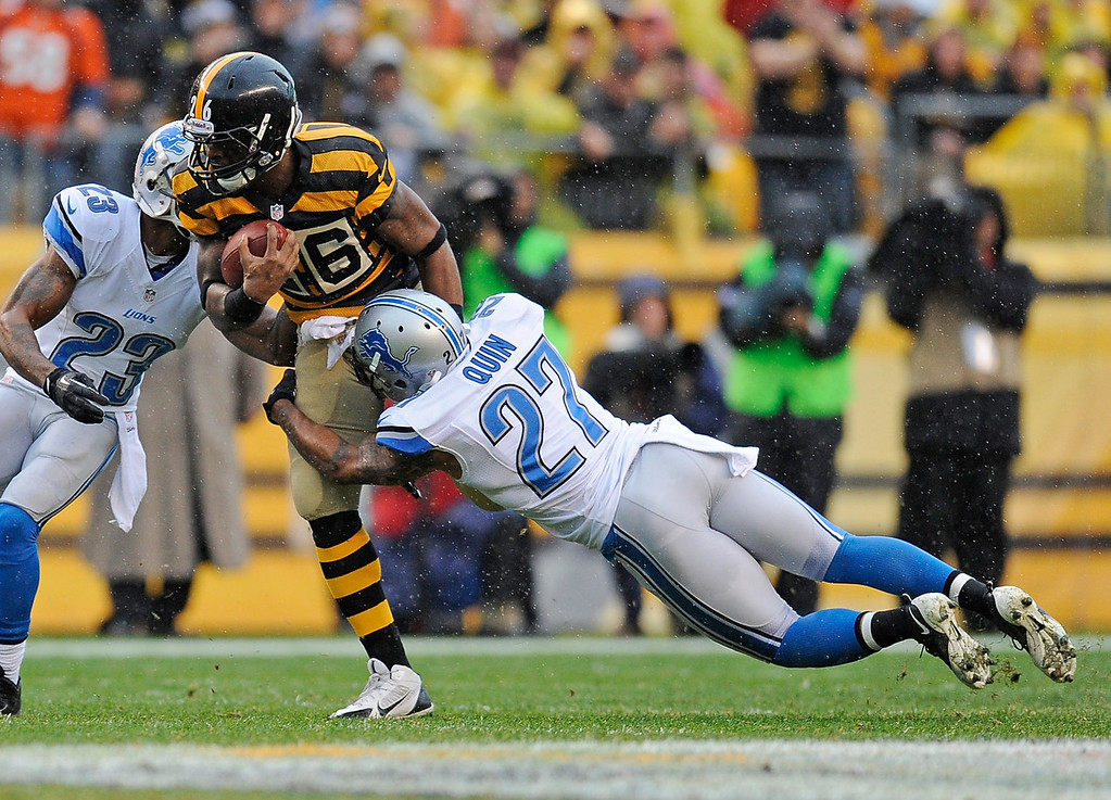 . Le\'Veon Bell #26 of the Pittsburgh Steelers is dragged down by Glover Quin #27 of the Detroit Lions on November 17, 2013 at Heinz Field in Pittsburgh, Pennsylvania.  (Photo by Joe Sargent/Getty Images)