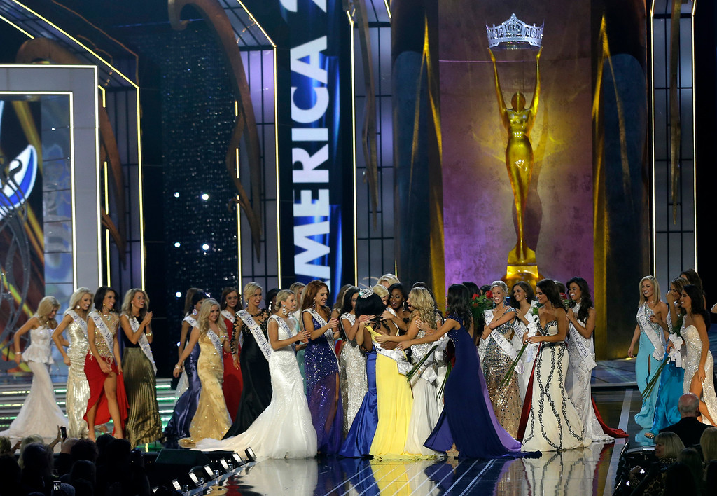. Miss New York Nina Davuluri, center left in yellow, is approached by contestants after Davuluri was crowned as Miss America 2014, Sunday, Sept. 15, 2013, in Atlantic City, N.J. (AP Photo/Mel Evans)