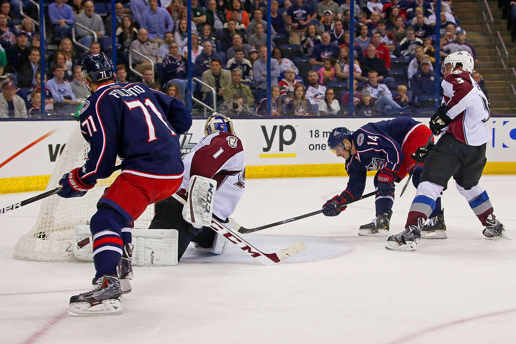 . COLUMBUS, OH - APRIL 1:  Blake Comeau #14 of the Columbus Blue Jackets slips past Nate Guenin #5 of the Colorado Avalanche and shoots the puck past Semyon Varlamov #1 of the Colorado Avalanche after receiving the pass from Nick Foligno #71 of the Columbus Blue Jackets during the second period on April 1, 2014 at Nationwide Arena in Columbus, Ohio. (Photo by Kirk Irwin/Getty Images)