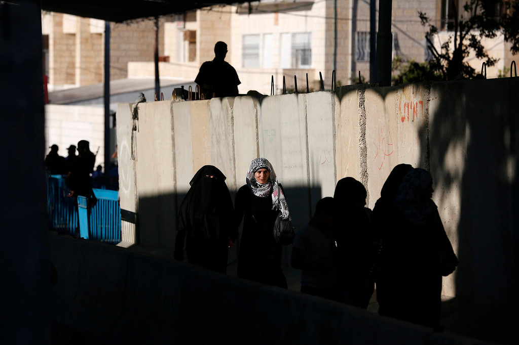 . Palestinian women cross at an Israeli checkpoint in the West Bank town of Bethlehem, during the holy month of Ramadan July 26, 2013.  REUTERS/Baz Ratner