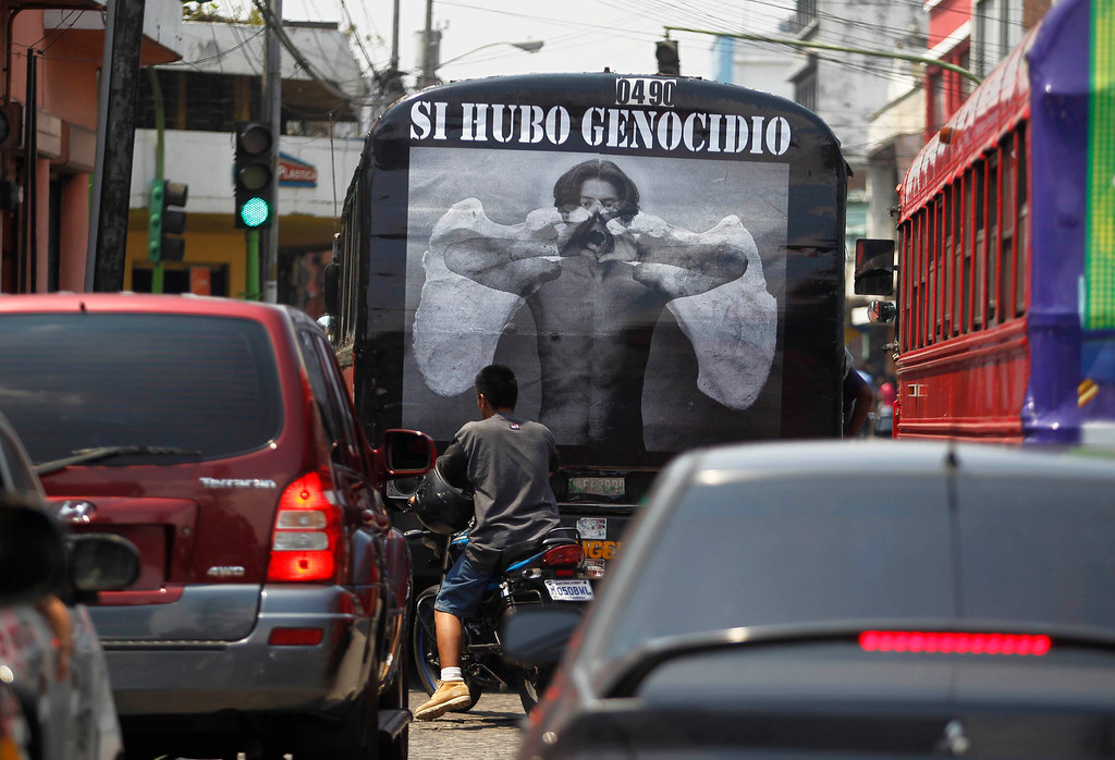 ". A man rides pass a poster on the back of bus at the streets of Guatemala City, May 8, 2013. During the internal armed conflict in Guatemala, between 1960 and 1996 around 200,000 people were forcibly disappeared or killed and that 669 massacres had taken place, mainly in Indigenous villages. The poster reads, ""Justice for Genocide\"". REUTERS/Jorge Dan Lopez"