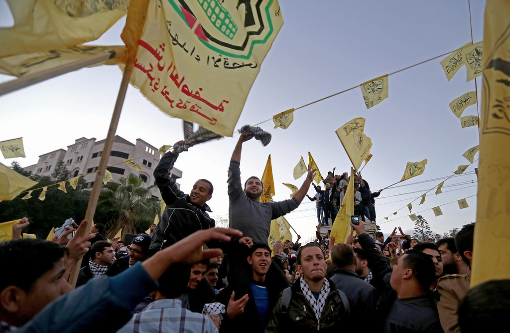 . Palestinians wave yellow Fatah flags during celebrations marking the 49th anniversary of the Fatah movement in Gaza City, Tuesday, Dec. 31, 2013. Fatah staged a massive rally Tuesday in the Gaza Strip, the Second such gathering in the territory since the Islamist Hamas group violently took control there in 2007.  (AP Photo/Hatem Moussa)