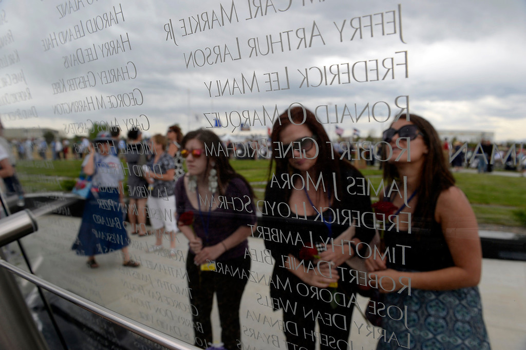 . From left, Marissa Baum, 18,  Lisa Hoskinson, 39, and Michelle Baum, 22, look for their cousin Ryan Baum\'s name on the glass after the dedication May 26, 2013 in Aurora.  (Photo By John Leyba/The Denver Post)