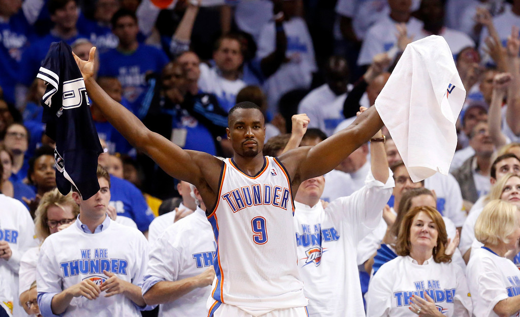 . Oklahoma City Thunder forward Serge Ibaka (9) celebrates after a three-point basket by teammate Derek Fisher late in the fourth quarter of Game 4 of the Western Conference finals NBA basketball playoff series against the San Antonio Spurs in Oklahoma City, Tuesday, May 27, 2014. Oklahoma City won 105-92. (AP Photo/Sue Ogrocki)