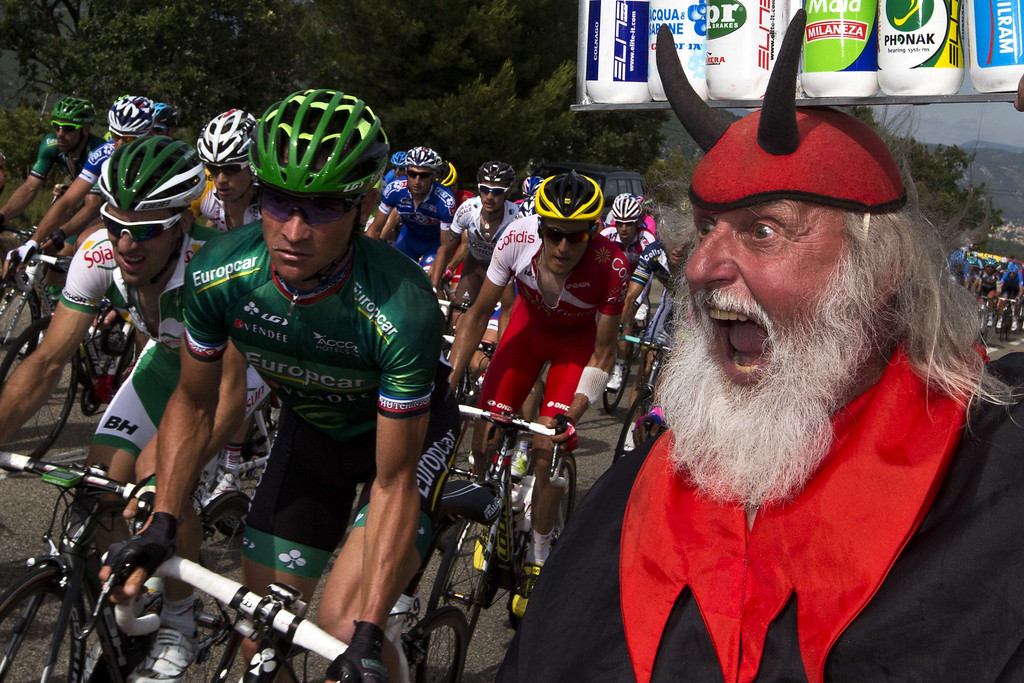 ". A disguised spectator ""El diablo\"" cheers riders as France\'s Thomas Voeckler rides past in the pack during the 228.5 km fifth stage of the 100th edition of the Tour de France cycling race on July 3, 2013 between Cagnes-sur-Mer and Marseille, southern France.   AFP PHOTO / JOEL  SAGET/AFP/Getty Images"