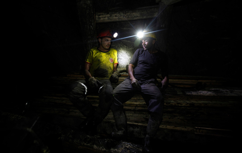 . In this Tuesday, Sept. 24, 2013 photo, miners rest inside the tunnel of La Flauta coal mine in Tausa, Colombia. Residents of this remote village in central Colombia pray every day that authorities don\'t close the small coal mines that have sustained them for as long as anyone can remember. They worry that La Flauta will be closed if authorities declare the area a nature reserve in which mining is prohibited. (AP Photo/Fernando Vergara)