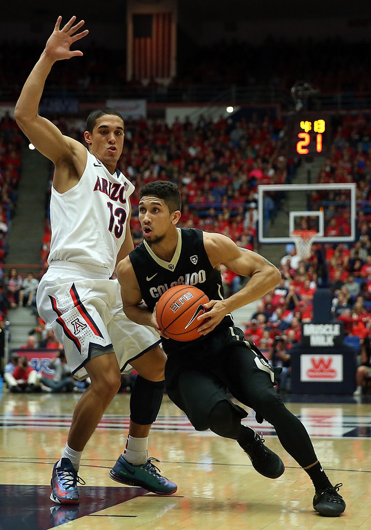 . Askia Booker #0 of the Colorado Buffaloes drives the ball against Nick Johnson #13 of the Arizona Wildcats during the second half of the college basketball game at McKale Center on January 23, 2014 in Tucson, Arizona. The Wildcats defeated the Buffaloes 69-57.  (Photo by Christian Petersen/Getty Images)