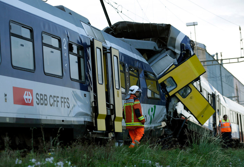. Rescue workers are pictured at the site of a head on collision between two trains near Granges-pres-Marnand, near Payerne in western Switzerland, July 29, 2013. The two trains collided at Granges-pres-Marnand in the Swiss canton of Vaud on Monday evening, injuring about 40 people, four seriously, Swiss news agency ATS reported. There was no immediate report of any deaths in the crash. REUTERS/Denis Balibouse