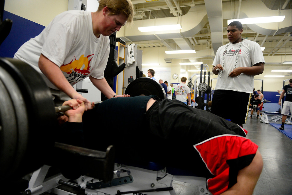 . Right tackle Isaiah Holland looks on with a chain around his neck as left guard Ryan Cummings does bench press reps of 315 pounds with a spot from left tackle Alec Ruth during practice. (Photo by AAron Ontiveroz/The Denver Post)