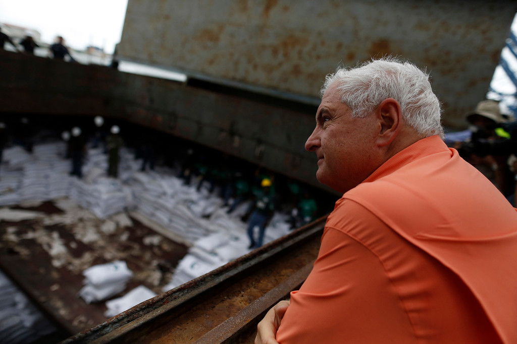 ". Panama\'s President Ricardo Martinelli look at bags labeled ""Cuban Raw Sugar\"" inside a North Korean flagged ship \""Chong Chon Gang\"" docked at the Manzanillo Container Terminal in Colon City July 16, 2013. REUTERS/Carlos Jasso"
