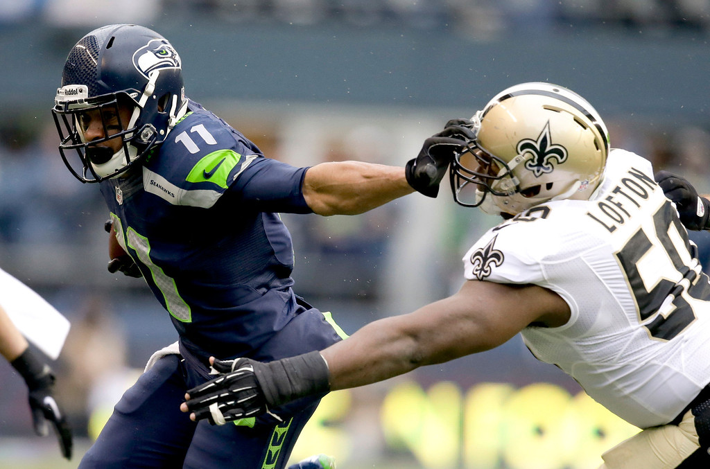 . Seattle Seahawks wide receiver Percy Harvin, left, fends off New Orleans Saints middle linebacker Curtis Lofton (50) during the first half of an NFC divisional playoff NFL football game in Seattle, Saturday, Jan. 11, 2014. (AP Photo/Elaine Thompson)