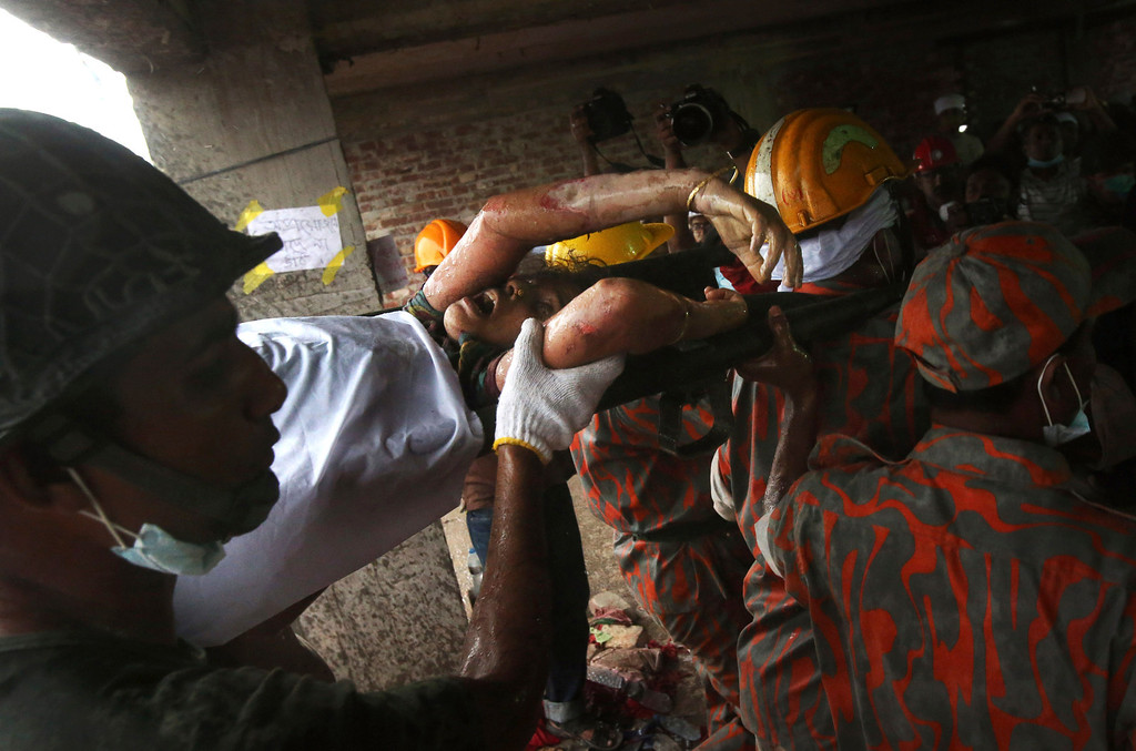 . A survivor is evacuated from a garment factory building that collapsed Wednesday in Savar, near Dhaka, Bangladesh, Saturday, April 27, 2013. Police in Bangladesh took five people into custody in connection with the collapse of a shoddily-constructed building this week, as rescue workers pulled 19 survivors out of the rubble on Saturday and vowed to continue as long as necessary to find others despite fading hopes.(AP Photo/Wong Maye-E)
