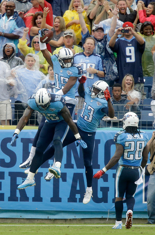 . Tennessee Titans wide receiver Justin Hunter (15) celebrates with Delanie Walker (82) and Kendall Wright (13) after Hunter caught a 16-yard touchdown pass against the New York Jets in the second quarter of an NFL football game on Sunday, Sept. 29, 2013, in Nashville, Tenn. Titans running back Chris Johnson (28) runs to join in. (AP Photo/Wade Payne)
