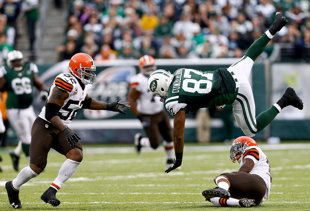 . EAST RUTHERFORD, NJ - DECEMBER 22:   Jeff Cumberland #87 of the New York Jets leaps over Tashaun Gipson #39 as D\'Qwell Jackson #52 of the Cleveland Browns closes in during their game at MetLife Stadium on December 22, 2013 in East Rutherford, New Jersey.  (Photo by Jeff Zelevansky/Getty Images)