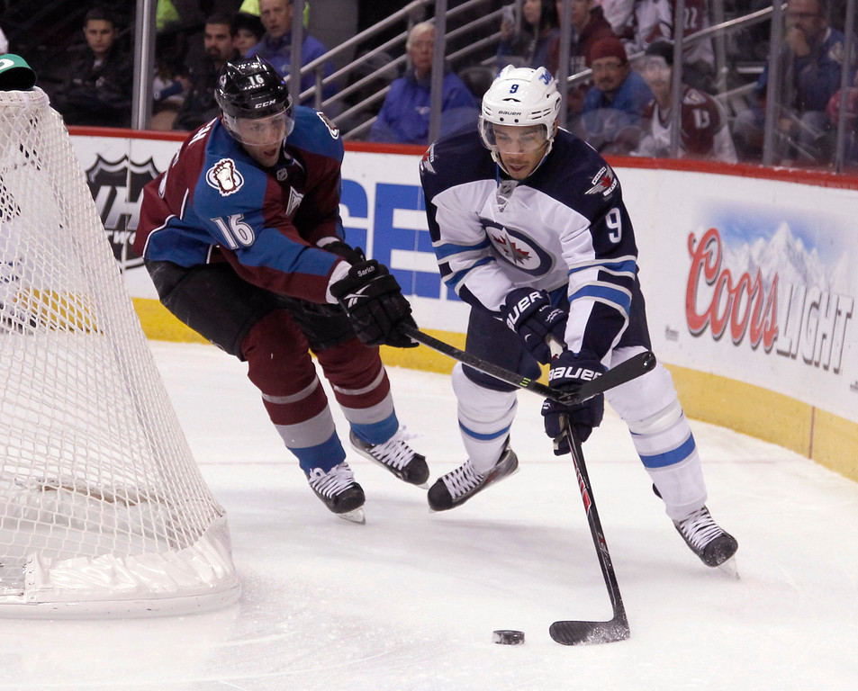 . Winnipeg Jets left wing Evander Kane, right, tries to wrap around the goal with the puck as Colorado Avalanche defenseman Cory Sarich covers in the first period of an NHL hockey game in Denver on Sunday, Oct. 27, 2013. (AP Photo/David Zalubowski)