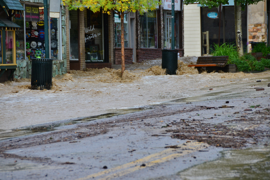 . Floodwater rages down Elkhorn Avenue Friday morning, Sept. 13, 2013 in downtown Estes Park. John Cordsen/Estes Park Trail-Gazette