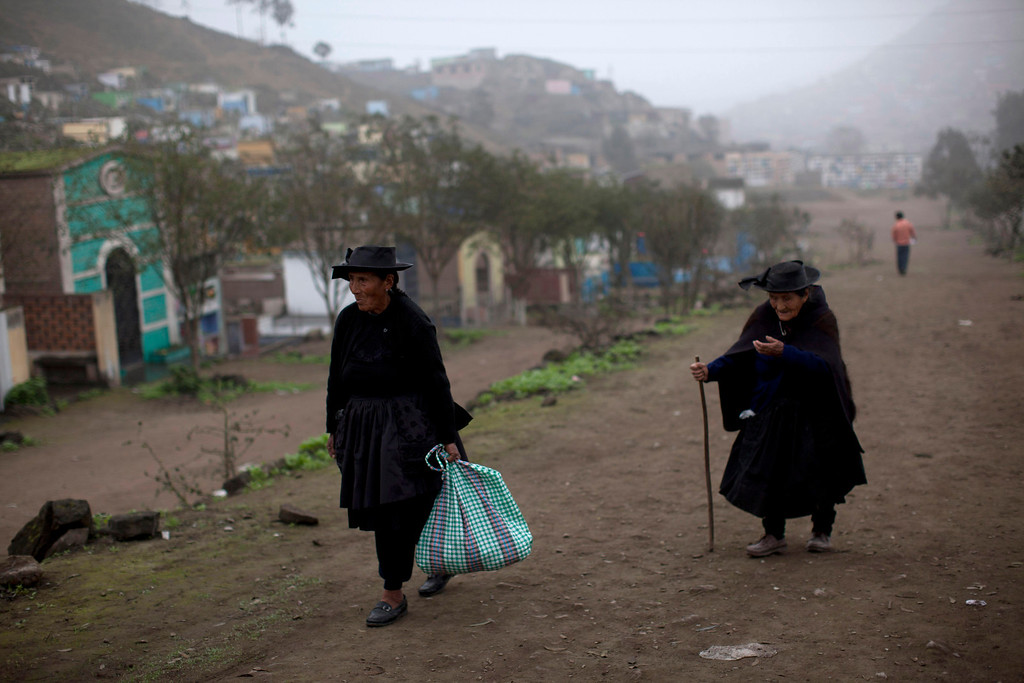 . In this Aug. 12, 2013 photo, two elderly women visit the Virgen de Lourdes cemetery in Lima, Peru. For roughly four months a year, the sun abandons Peru\'s seaside desert capital, suffocating it under a ponderous gray cloudbank and fog that coats the city with nighttime drizzles. Limenos don scarfs and jackets and complain of slipping into a gloom of seasonal depression. (AP Photo/Rodrigo Abd)