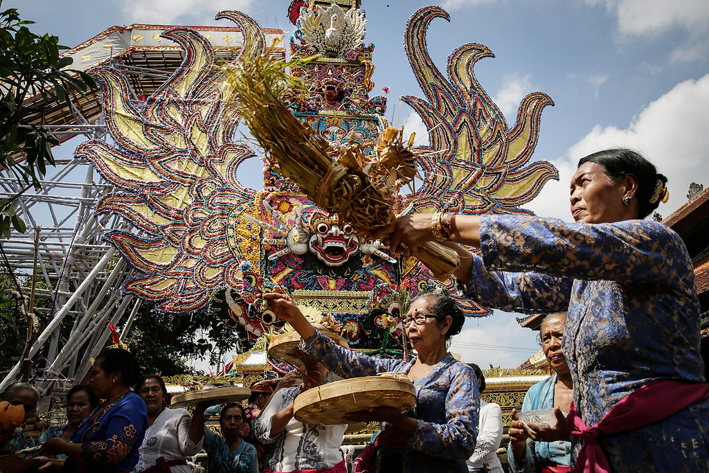 """. Balinese women give an offering and sprinkle holy water in front of the \""""Bade\"""" (body carrying tower) during the Royal cremation ceremony on November 1, 2013 in Ubud, Bali, Indonesia. (Photo by Agung Parameswara/Getty Images)"""