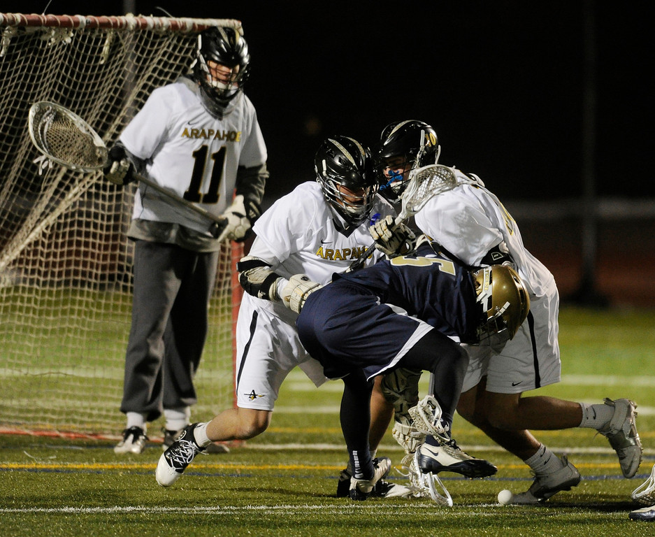 . LITTLETON, CO. - APRIL 10: Mullen senior attack Austin Smith (5) fought for the ball in front of the Warriors net in the second half. The Mullen High School boy\'s lacrosse team defeated Arapahoe 8-7 Wednesday night, April 10, 2013. Photo By Karl Gehring/The Denver Post)