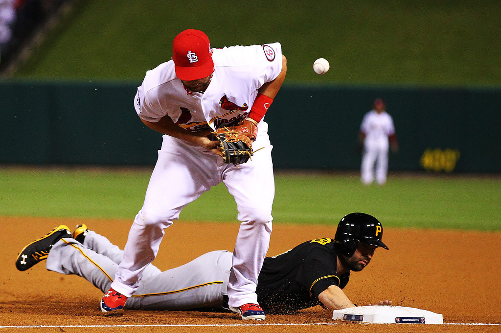 . Neil Walker #18 of the Pittsburgh Pirates dives back to first base safe as Matt Adams #53 of the St. Louis Cardinals attempts to complete the pickoff in the first inning during Game Five of the National League Division Series at Busch Stadium on October 9, 2013 in St Louis, Missouri.  (Photo by Dilip Vishwanat/Getty Images)