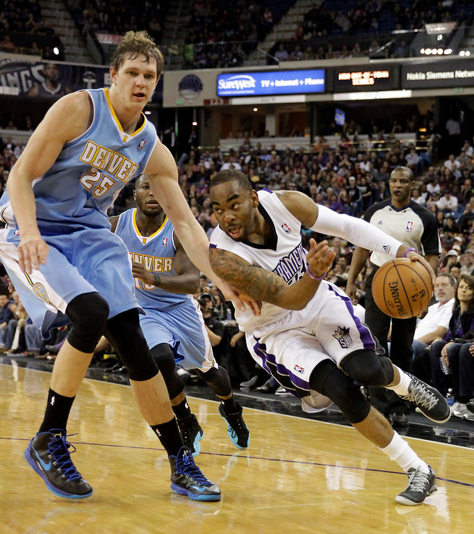 . Sacramento Kings guard Marcus Thornton, right, drives against Denver Nuggets center Timofey Mozgov, of Russia,  during the fourth quarter of an NBA basketball game in Sacramento, Calif., Sunday, Jan. 26, 2014. The Nuggets won 125-117.(AP Photo/Rich Pedroncelli)
