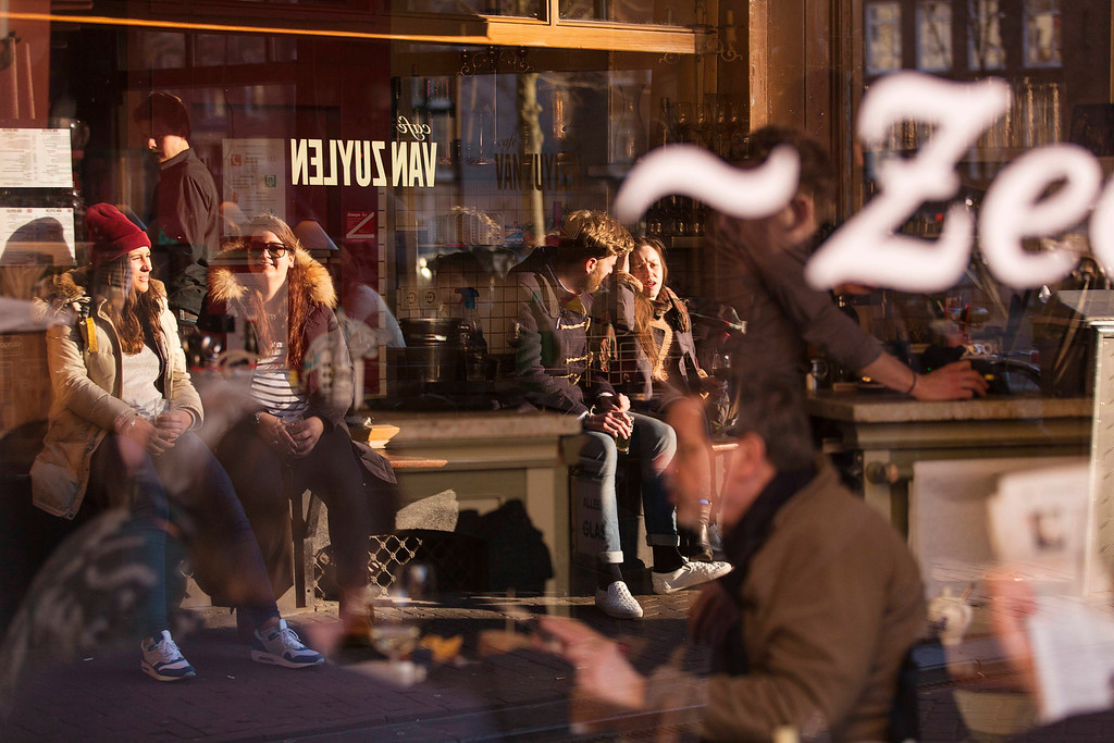 . Visitors of a local cafe are reflected in a window in Amsterdam April 2, 2013, 2013. The Royal celebrations in the Netherlands this week put the country and the capital Amsterdam on front pages and television screens around the world with an orange splash. There\'s plenty to see and do in 48 hours in this compact city, where the world-famous Rijksmuseum only recently reopened after an extensive renovation. Picture taken April 2, 2013. REUTERS/Michael Kooren