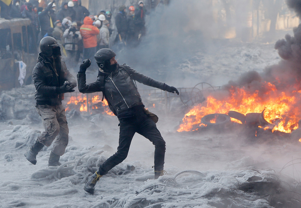 . Protesters throw stones towards riot police during a clash in central Kiev, Ukraine, Saturday Jan. 25, 2014. Ukraine\'s Interior Ministry has accused protesters in Kiev of capturing two of its officers as violent clashes have resumed in the capital and anti-government riots spread across Ukraine. (AP Photo/Efrem Lukatsky)