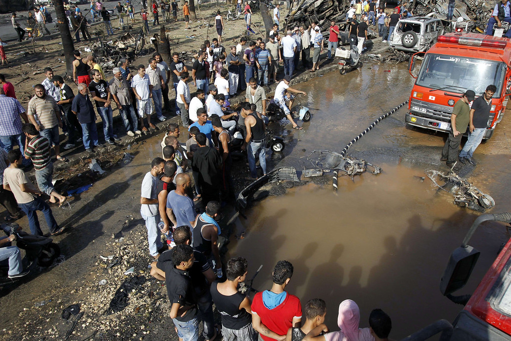 . Lebanese civilians gather next to a crater at the site of a blast outside the Al-Taqwa mosque in the northern city of Tripoli on August 23, 2013.  AFP PHOTO/ANWAR AMRO/AFP/Getty Images