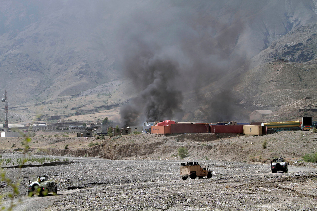 . Afghan Border Police vehicles head towards a base where NATO supply trucks are burning following an attack by militants in the Torkham area near the Pakistan-Afghanistan border in the Jalalabad province east of Kabul, Afghanistan, Monday, Sept. 2, 2013. The Taliban claimed responsibility for the strike on a U.S. base in Afghanistan near the border with Pakistan on Monday, setting off bombs, torching vehicles and shutting down a key road used by NATO supply trucks, officials said. Several people were killed.   (AP Photo/Rahmat Gul)