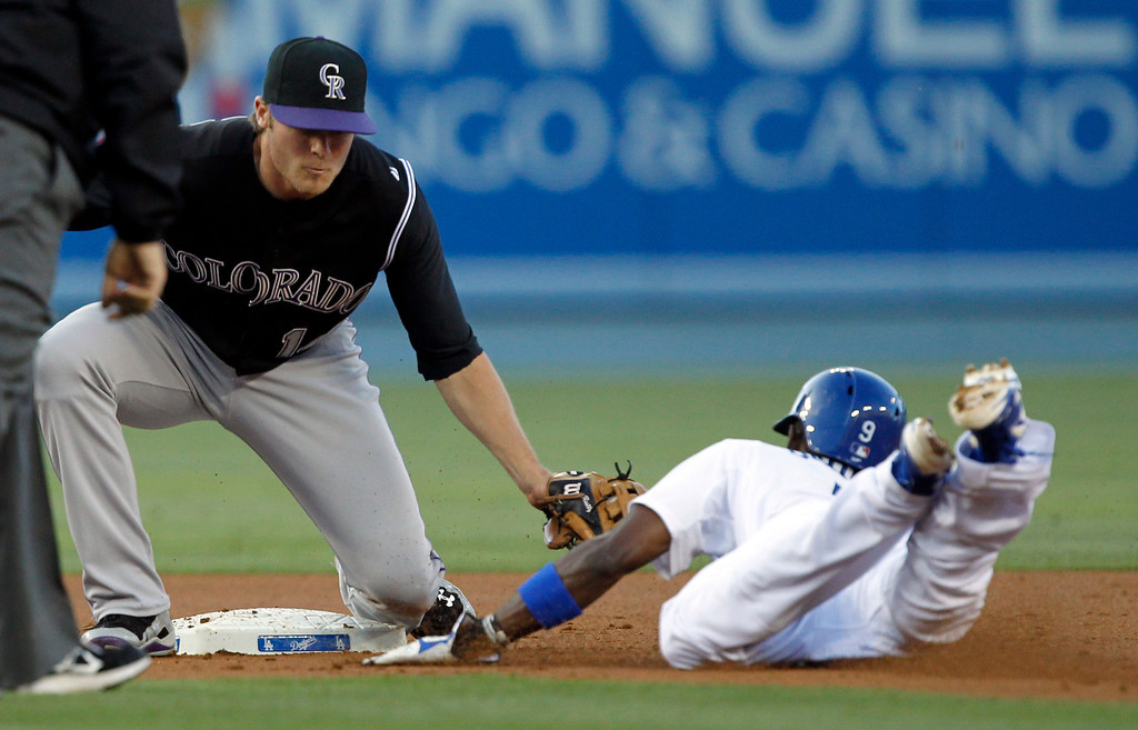 . Colorado Rockies second baseman Josh Rutledge, left, tags out Los Angeles Dodgersí Dee Gordon, right, attempting to steal second base in the first inning of a baseball game on Monday, June 16, 2014, in Los Angeles. (AP Photo/Alex Gallardo)