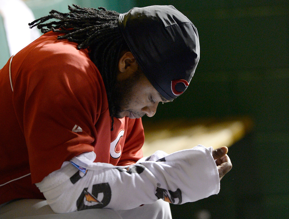 . Cincinnati Reds starting pitcher Johnny Cueto sits on the bench in the fourth inning of the NL wild-card playoff baseball game against the Pittsburgh Pirates on Tuesday, Oct. 1, 2013, in Pittsburgh. (AP Photo/Don Wright)