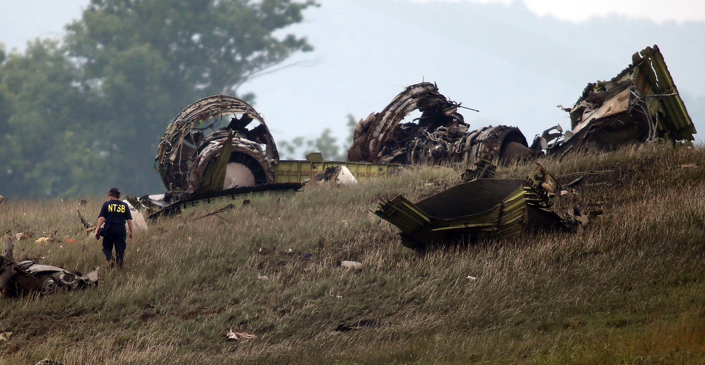 . A National Transportation Safety Board investigator looks over the debris of a UPS A300 cargo plane after it crashed on approach at Birmingham-Shuttlesworth International Airport, Wednesday Aug. 14, 2013, in Birmingham, Ala. The two pilots aboard the aircraft were killed. (AP Photo/Hal Yeager)
