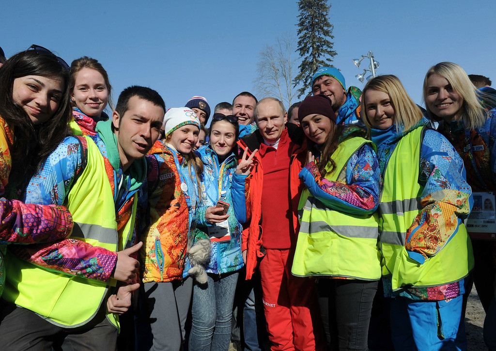 . Russian President Vladimir Putin (C) poses for a picture with volunteers as he attends the Men\'s 4x10 km Relay competition at the Sochi 2014 Olympic Games, Krasnaya Polyana, Russia, 16 February 2014.  EPA/MIKHAIL KLIMENTIEV/RIA NOVOSTI/K