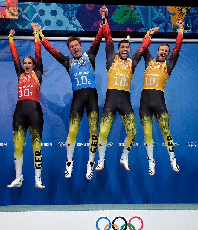 . The German team of Natalie Geisenberger, in orange, Felix Loch, in blue, and doubles team of Tobias Wendl and Tobias Arlt, in yellow, leap onto the podium after winning the gold medal during the luge team relay competition at the 2014 Winter Olympics, Thursday, Feb. 13, 2014, in Krasnaya Polyana, Russia. (AP Photo/Michael Sohn)