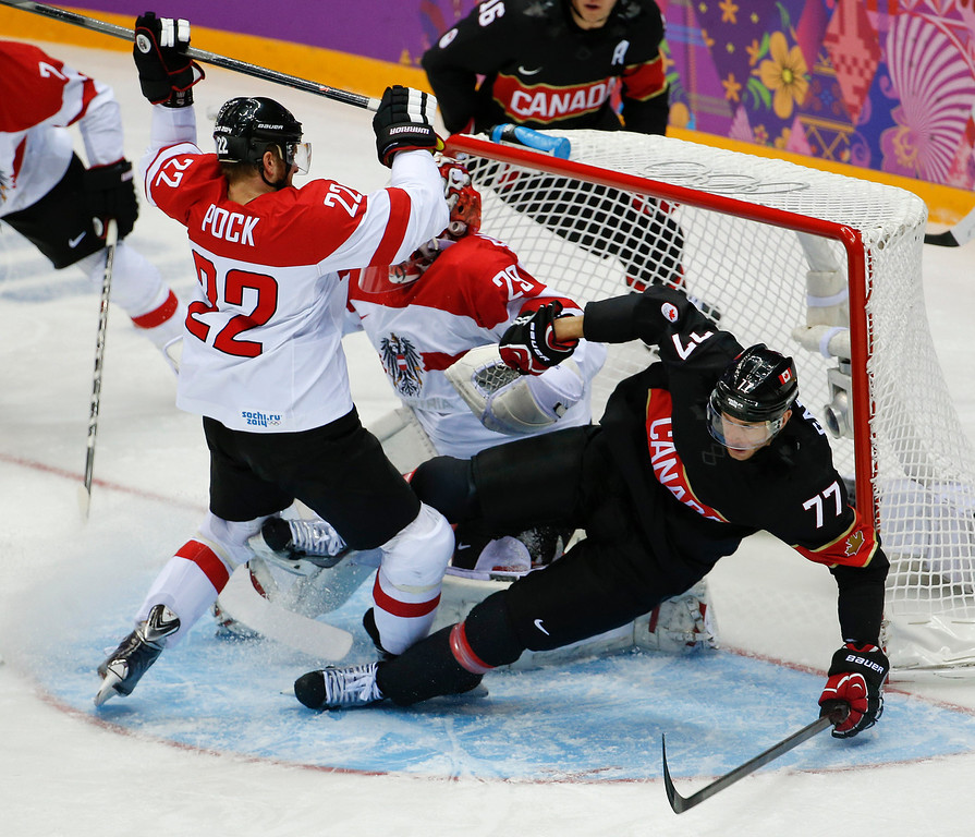 . Canada forward Jeff Carter collides with Austria defenseman Thomas Pock in the first period of a men\'s ice hockey game at the 2014 Winter Olympics, Friday, Feb. 14, 2014, in Sochi, Russia. (AP Photo/Julio Cortez)