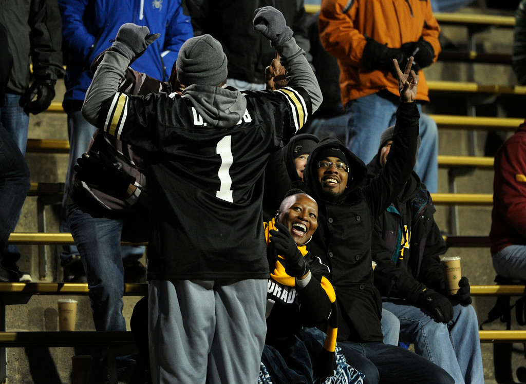 . BOULDER, CO - NOVEMBER 23: As they see themselves on the stadium large-screen, Kevin Scott, the uncle of senior Derrick Webb, a linebacker for the Colorado Buffaloes football team, turns and points to his nephew\'s jersey while Derrick\'s mother Felicia Morris, center, and the fiancé of Derrick\'s sister, Mikel Brookins join in the fun just before the start of the second half in the game against the Southern California Trojans at Folsom Field in mid-November. It is senior day and the last home game of the season, and each senior player is recognized and greeted by family and friends on the field. (Photo by Kathryn Scott Osler/The Denver Post)