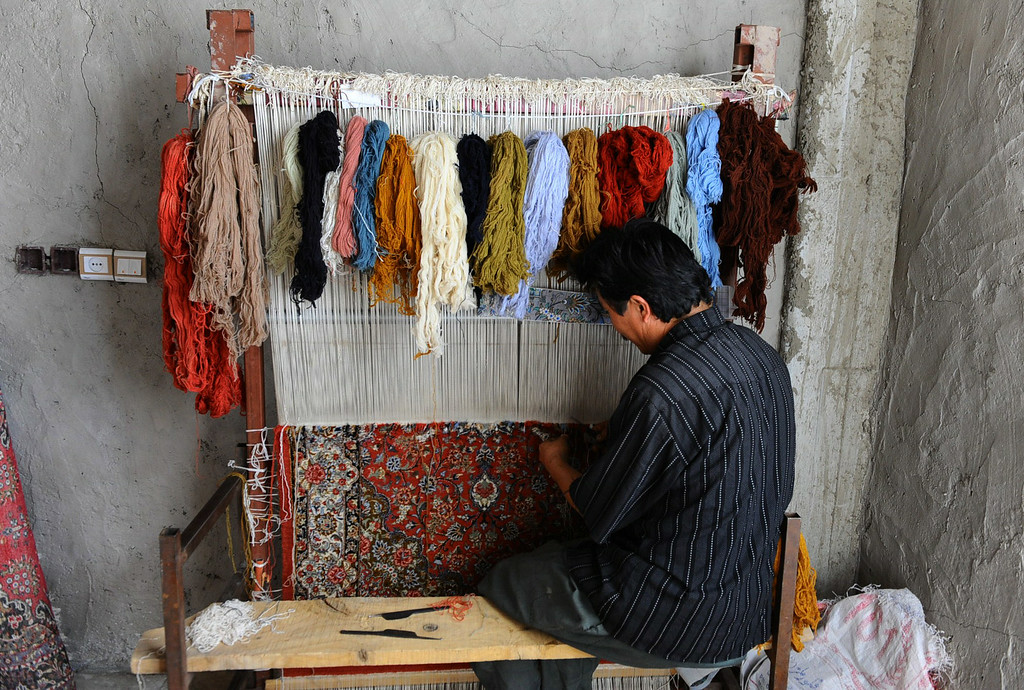 . In this picture taken on June 25, 2014, an Afghan worker weaves a carpet at a traditional factory in Herat. AFP PHOTO/Aref Karimi/AFP/Getty Images