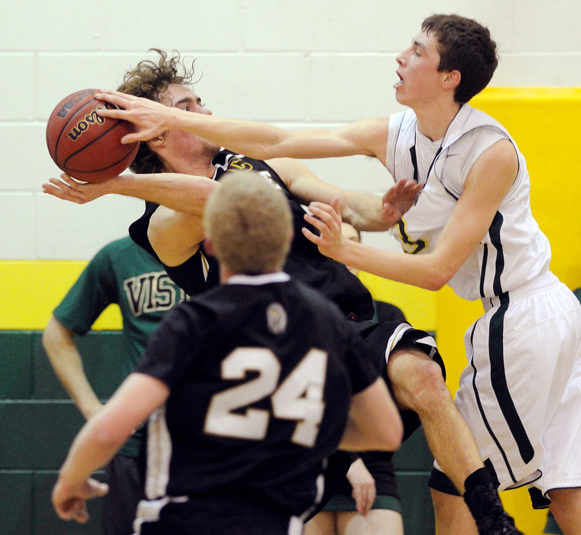 . Mountain Vista guard Jake Pemberton (3) blocked a shot from Arapahoe senior Taven Sparks (15) in the first half. The Mountain Vista High School boy\'s basketball team hosted Arapahoe Friday night January 4, 2013.  Karl Gehring/The Denver Post