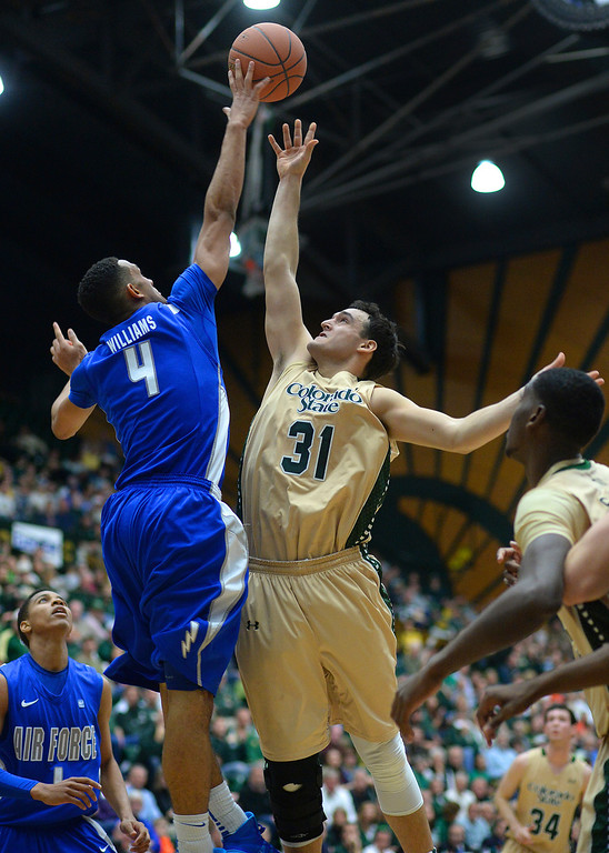 . FORT COLLINS, CO. - JANUARY 18:  Air Force junior forward Kamryn Williams (4) rejected a shot by Rams\' forward J.J. Avila (31) in the second half. The Colorado State men\'s basketball team defeated Air Force 74-68 at Moby Arena in Fort Collins Saturday night, January 18, 2014. Photo By Karl Gehring/The Denver Post